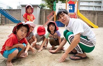 砂遊びをする園児と先生