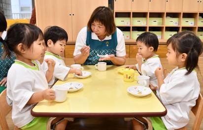 おやつを食べる園児と先生